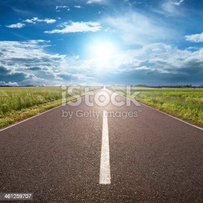 Driving on an empty road towards the sun