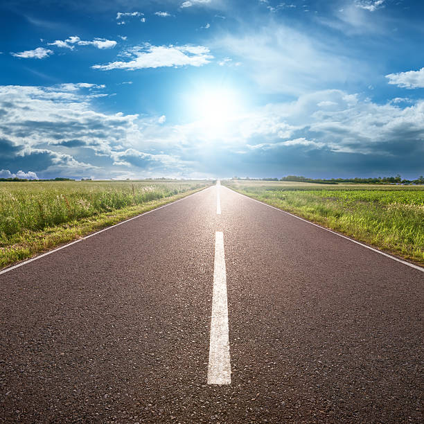 asphalt road leading to horizon with grass and blue sky - straight stock photos and pictures