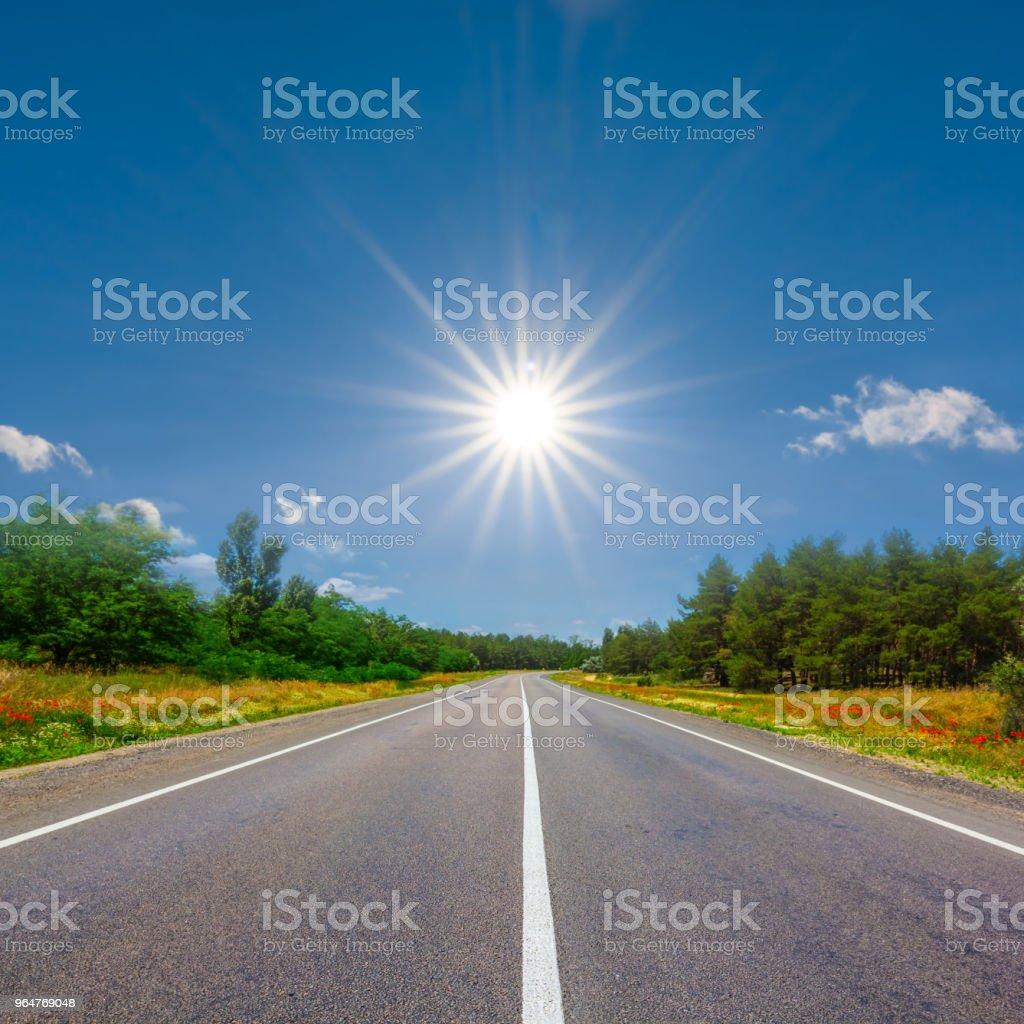 asphalt road leaving far  to a sparkle sun royalty-free stock photo