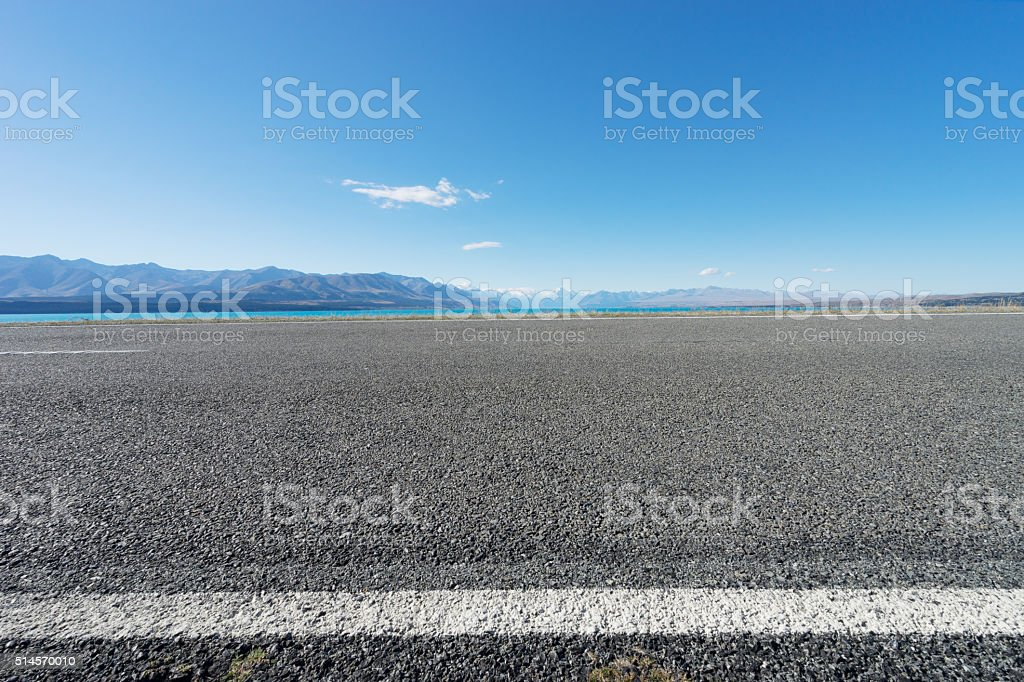 asphalt road near lake in summer day in New Zealand stock photo