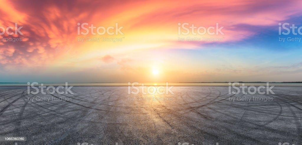 Asphalt road pavement and dramatic sky with coastline - Foto stock royalty-free di Acqua