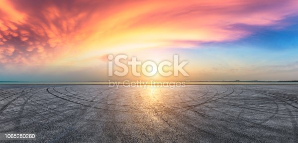 Asphalt road pavement and dramatic sky with coastline at sunset