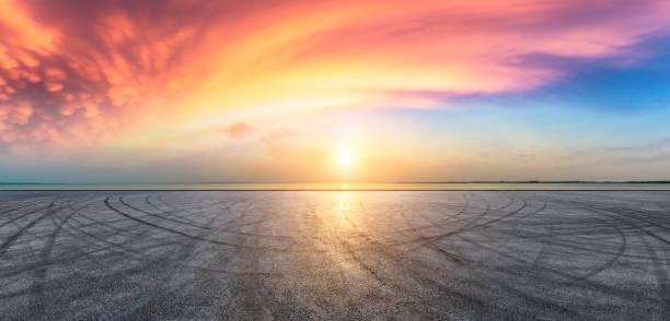 pavimento de camino de asfalto y cielo dramático con costa - vía fotografías e imágenes de stock