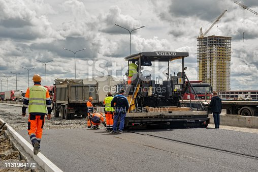 Tyumen, Russia - June 1, 2017: JSC Mostostroy-11. Construction of two-level outcome on bypass road on Fedyuninskogo and Permyakova streets intersection. Asphalt road paver paving machine