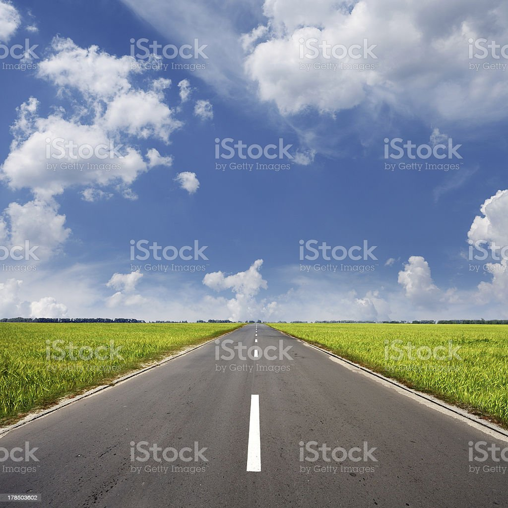 asphalt road through the green field and clouds stock photo