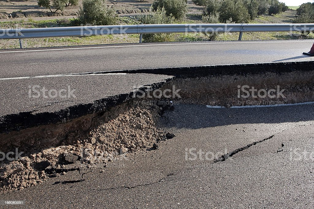 Asphalt road with a crack caused by landslides royalty-free stock photo