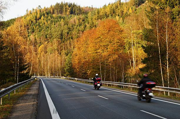 asphalt road with a ride motorcycles in the autumn landscape - motorcykel bildbanksfoton och bilder