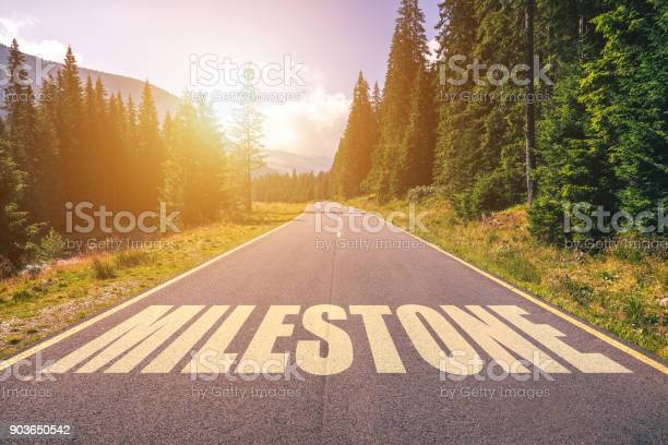 Photo of Asphalt road with arrow guideline and Milestone letters painted on the surface. An image of a road milestones are representative of success in the future goal. Road to success with light of the sun