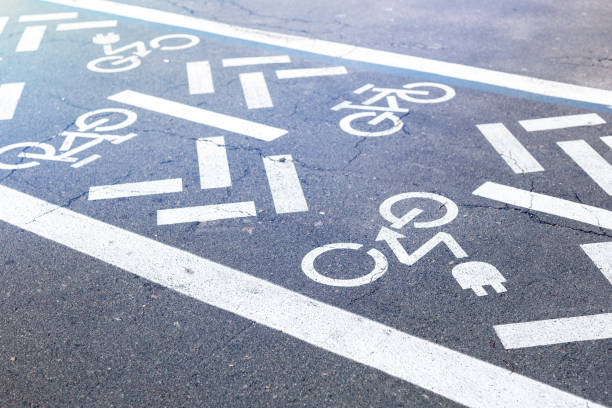 Asphalt road with bicycle and electric transport lane. Cycle and zero emission vehicles white sign on floor. Recreation area for green energy transport in city park stock photo