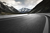 istock Asphalt road with snow capped mountains background 679836614