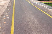 Asphalt road with two yellow lines and sidewalk mark  , white and