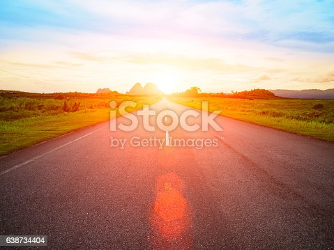 asphalt road with yellow blue sky background and Lens Flare or sunspot during sunset