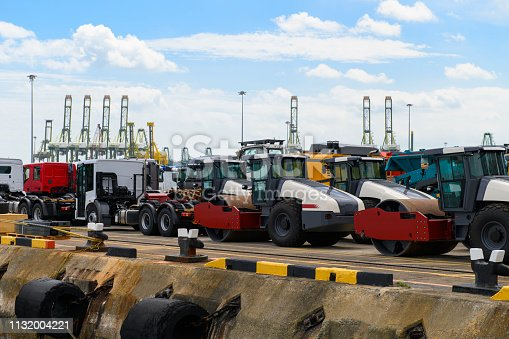 istock Asphalt roller and trucks waiting loading on a ship for import or export 1132004221