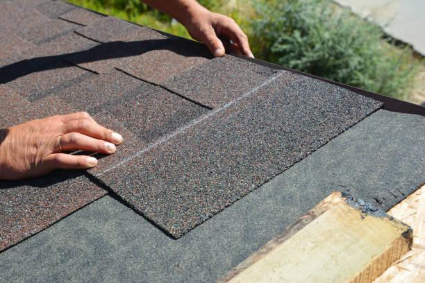 Asfalt gordelroos installatie. Roofer aannemer het installeren van asfalt gordelroos op huis dakbedekking constructie foto