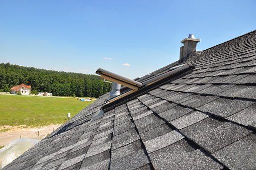 Asphalt shingles roof with open attic skylight window and unfinished roof chimney