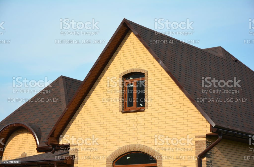 Asphalt Shingles Roofing Advantages. Roofing Construction House Building with Asphalt Shingles and Different Types of Roof Design. stock photo