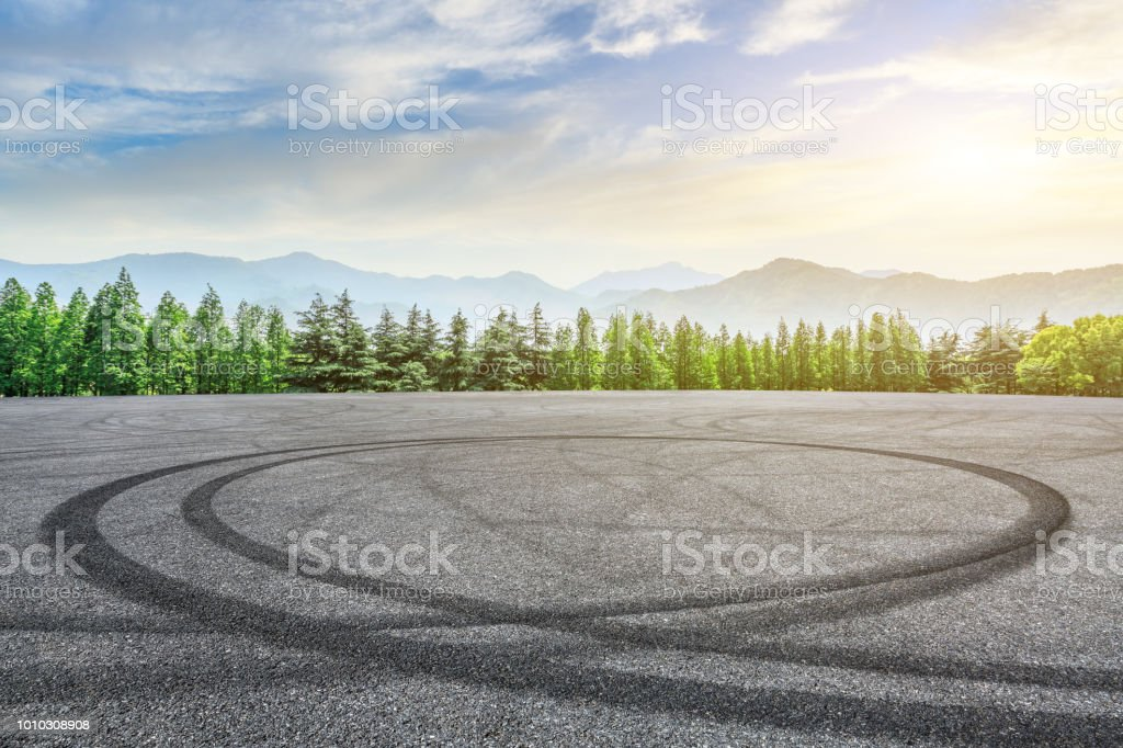 Empty asphalt square and mountain with forest scenery at sunrise