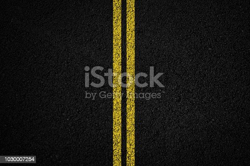 Double yellow line on black asphalt background