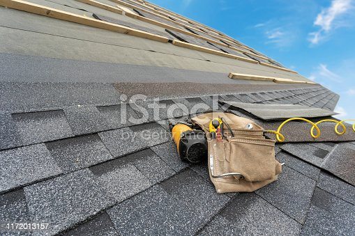 Tool belt with cutter knife and pneumatic nail gun on layer of installing asphalt or bitumen shingle on top of the new roof under construction residential house or building