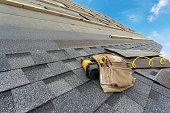 istock Asphalt tile roof and tool belt lying on new house under construction 1172013157