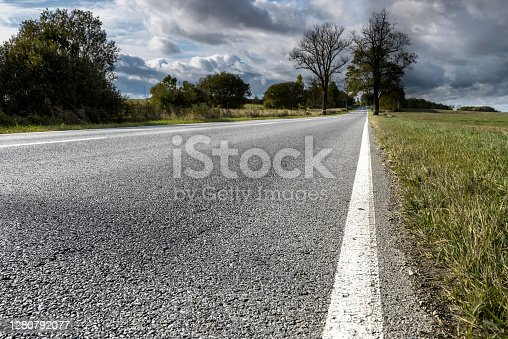 istock Asphalt transport road in the countryside of the Kaliningrad region on a cloudy day. 1280792077