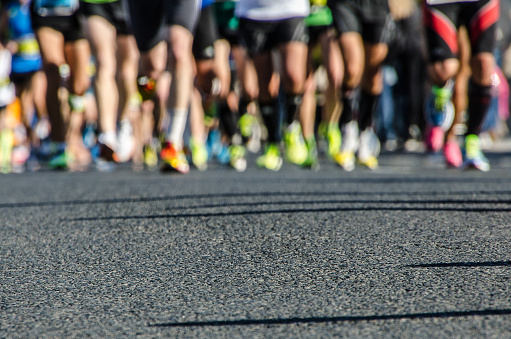 Asphalt with legs bottom of runners during the marathon of Valencia