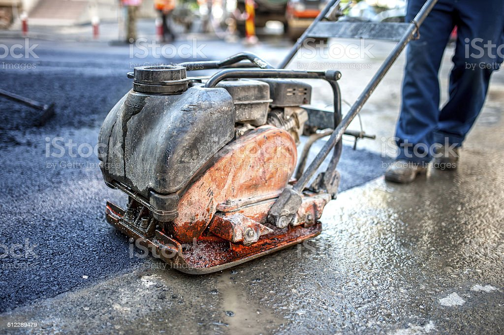 asphalt worker at road construction site with compactor plate stock photo