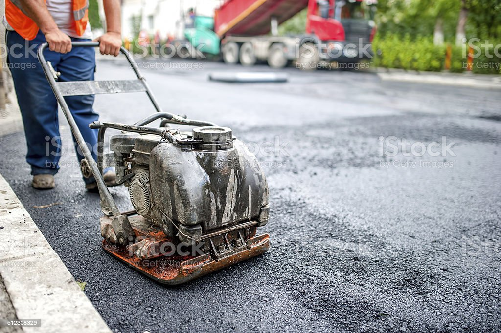 asphalt worker at road repairing and construction site, compactor plate stock photo