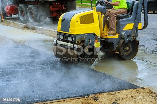 Asphalting construction works with commercial repair equipment road parking for the car with roller compactor machine