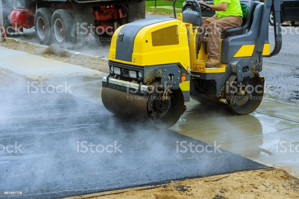 Asphalting construction works with commercial repair equipment road crews stock photo