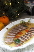 Aspic of the tongue decorated with boiled carrots and parsley on a festive background. Rustic style, selective focus.