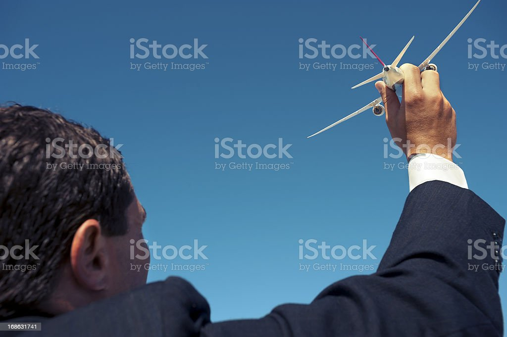 Aspiration concept. Businessman holding an airplane royalty-free stock photo