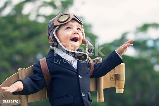 Aspiration, innovation business concept. A young smiling child wearing home made costume of a traditional pilots outfit complete with eye goggles and cap with ear flaps. A blurry background of natural greenery places the child in sharp focus, allowing for focus on the cardboard plane strapped into his back.