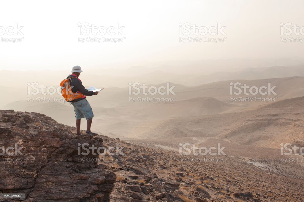 Aspirations for adventure. Reading map and looking on horizon over desert landscape. stock photo