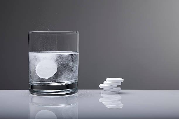 Aspirin paracetamol pill splashing into glass of water stock photo