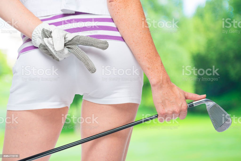 Ass golfer close-up with golf club in hand on a background of golf courses stock photo