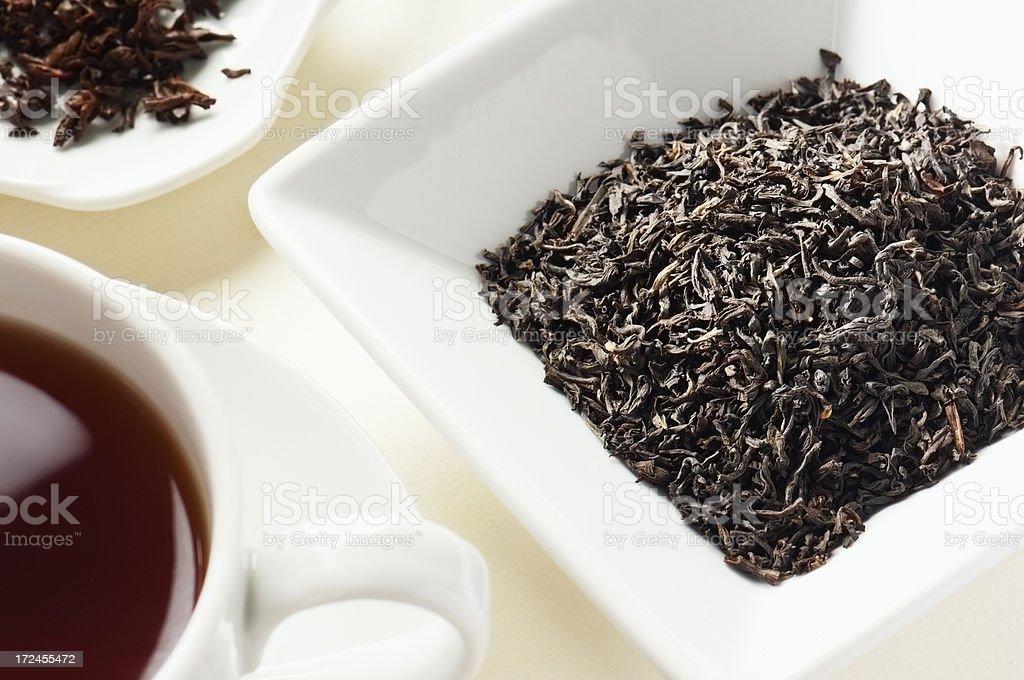 Assam Tea Leaves tea leaves behind cup of tea stock photo