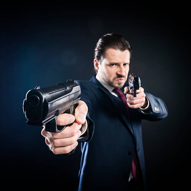 Assassin, gangster suit aiming with two guns, mafioso, killer, mafia stock photo