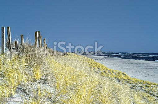 High winds and a cold front result in rough seas pounding the maryland assateague state park seashore, a barrier island earning its designation with the resort tourist town of ocean city maryland on the horizon and the dune grass being replanted to protect the island