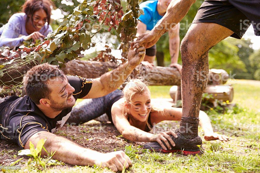 Assault course competitor helping others crawl under nets stock photo
