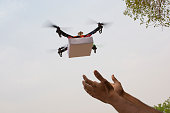 Assembled Drone quadcopter delivering a package and hands receiving the parcel.