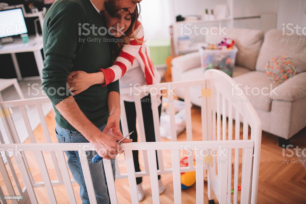 Young couple, who is expecting a baby, assembling a baby crib in...