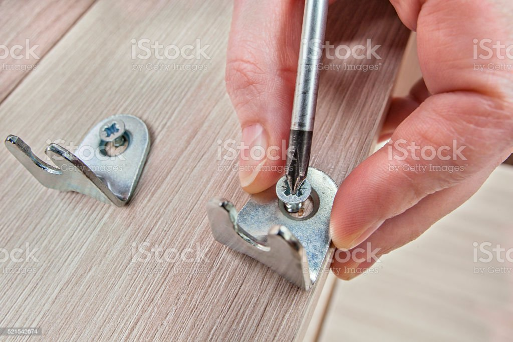 Assembling furniture, bracket screwing screw  using phillips head screwdriver, close-up. stock photo