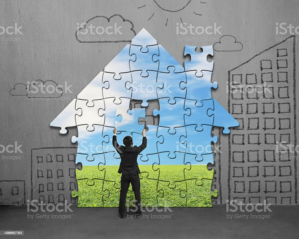 Assembling house shape puzzles on wall stock photo