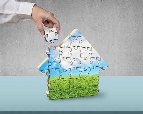 Assembling house shape puzzles on desk