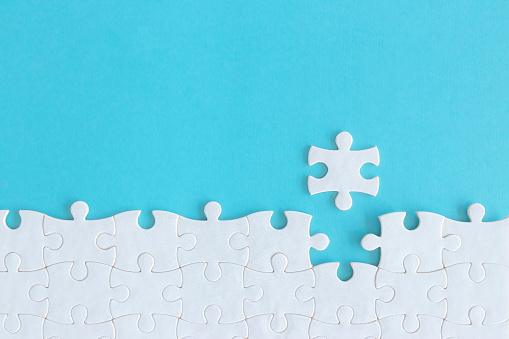 Assembling jigsaw puzzle pieces, Top view unfinished white jigsaw puzzle on blue background, Fragment of a folded white jigsaw puzzle with copy space, Teamwork and problem solving concept.