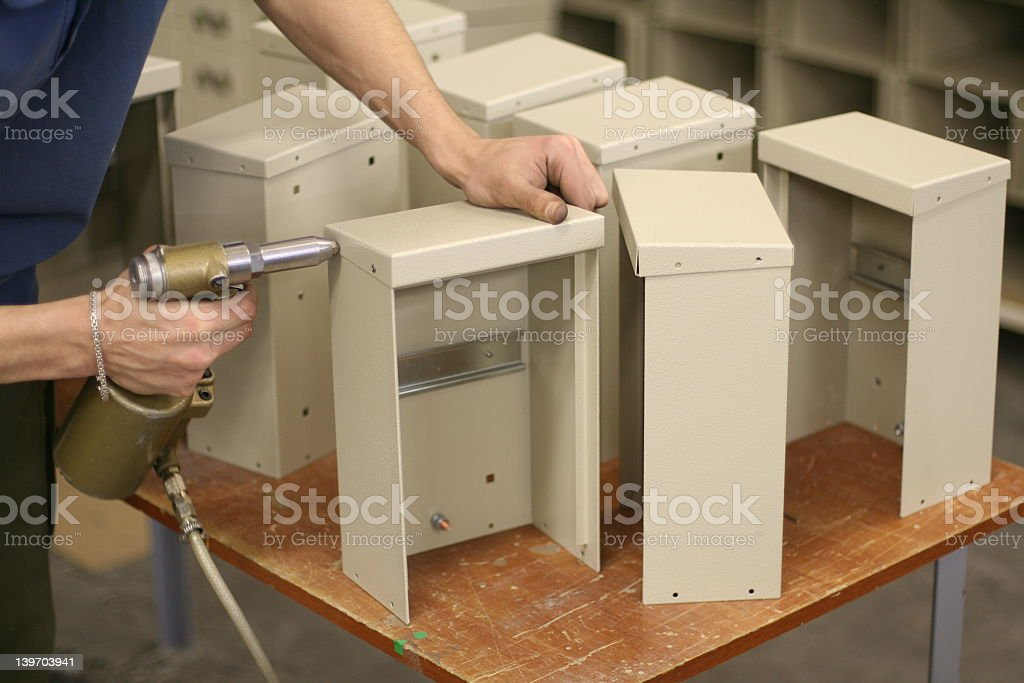 Assembling many metal pieces together stock photo