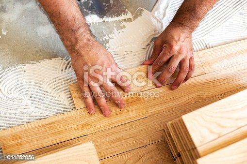 922081754istockphoto Assembling of parquet floor in progress 1044252856