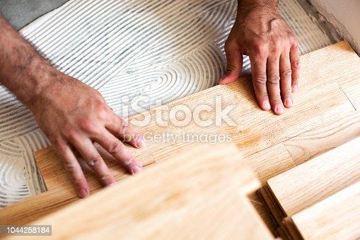 922081754istockphoto Assembling of parquet floor in progress 1044258184