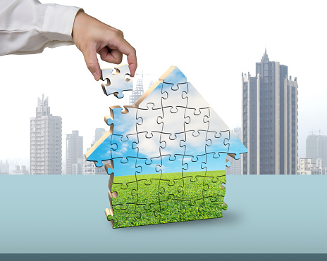 Assembling puzzles in house building shape in office